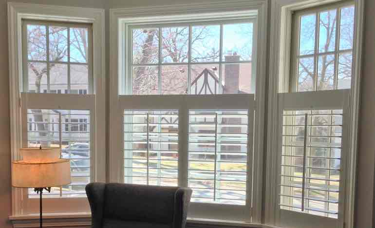 Half insulating shutters in living room bay window.