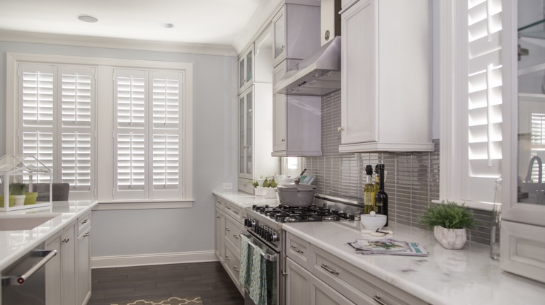 Plantation shutters in New York City kitchen with modern appliances.