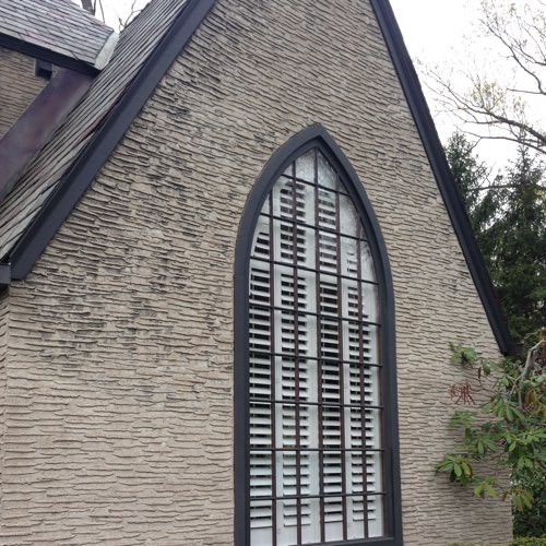 outside view of stone home with plantation shutters