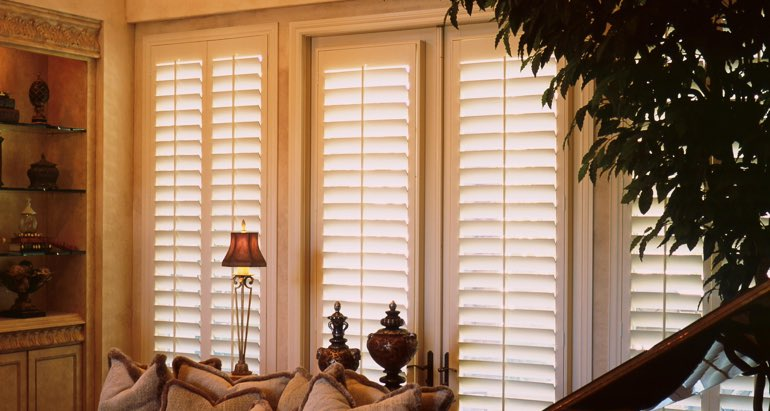 Plantation shutters on windows and door in Hartford living room
