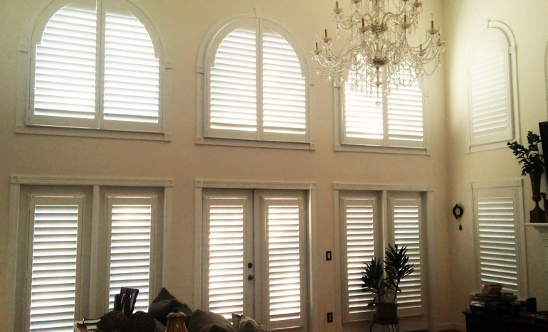 Family room in two-story Hartford home with plantation shutters on tall windows.