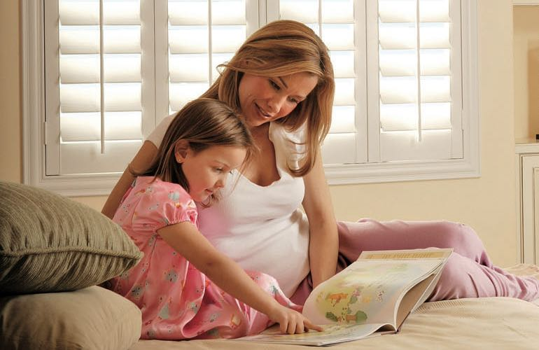 Mom and daughter reading on bed with shuttered windows.