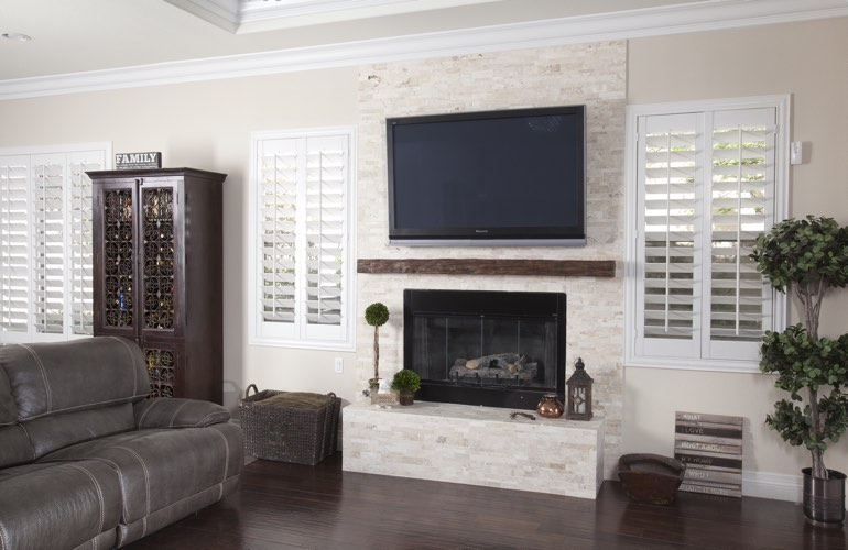 White plantation shutters in a New York City living room with solid hardwood floors.