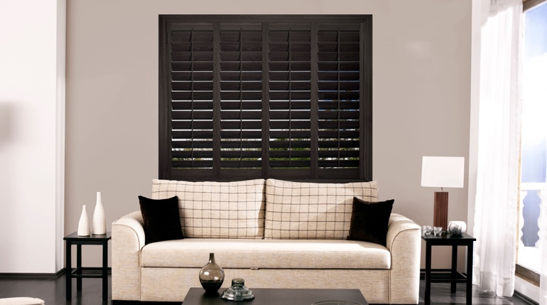 New York City sitting room with stained wood shutters.
