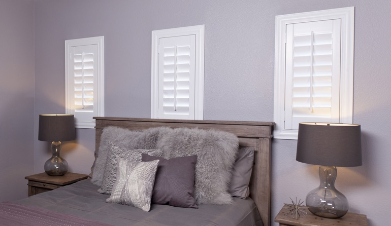 White plantation shutters in New York City bedroom windows.