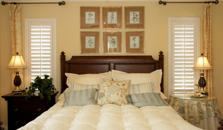Tall plantation shutters framing bed in a bedroom in New York City