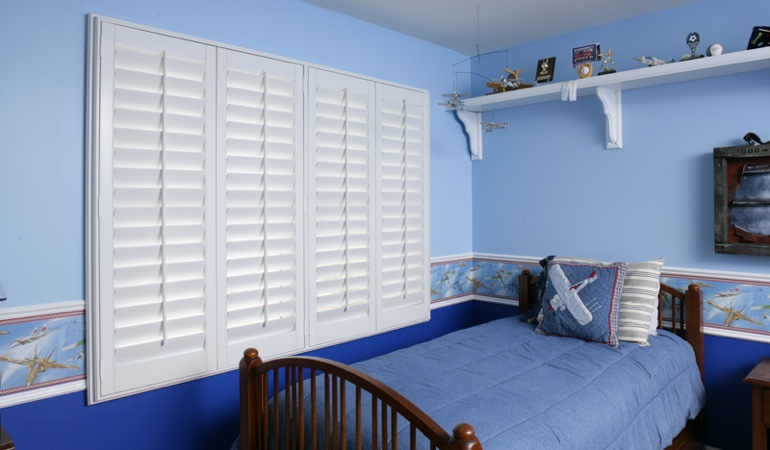 Blue kids bedroom with white plantation shutters in New York City
