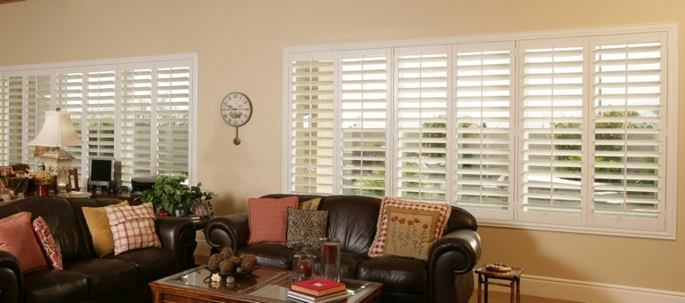 Wide window with interior shutters in New York City living room